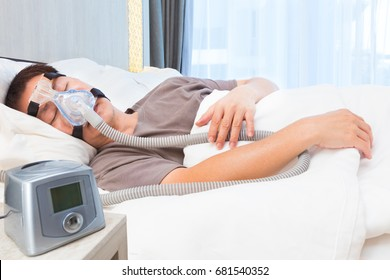 middle age asian man sleeping in his bed wearing CPAP mask connecting to air hose and CPAP machine, device for people with sleep apnea