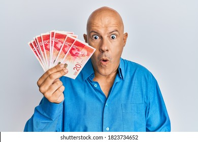 Middle age bald man holding 20 israel shekels banknotes scared and amazed with open mouth for surprise, disbelief face