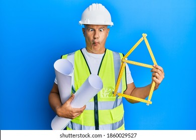 Middle age bald man wearing architect hardhat holding build project making fish face with mouth and squinting eyes, crazy and comical.