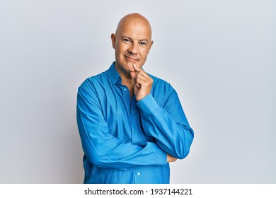 Middle age bald man wearing casual clothes smiling looking confident at the camera with crossed arms and hand on chin. thinking positive.