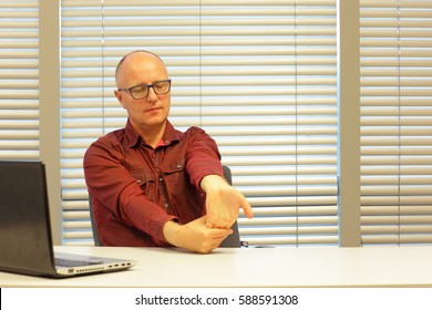middle age balding man  stretching arm - short break for exercise on chair in office