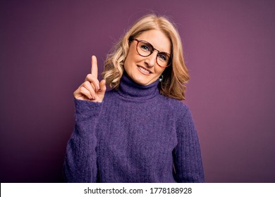 Middle age beautiful blonde woman wearing casual purple turtleneck sweater and glasses showing and pointing up with finger number one while smiling confident and happy.