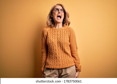 Middle age beautiful blonde woman wearing casual sweater and glasses over yellow background angry and mad screaming frustrated and furious, shouting with anger. Rage and aggressive concept.