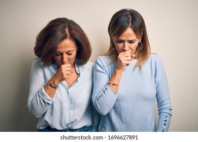 Middle age beautiful couple of sisters standing over isolated white background feeling unwell and coughing as symptom for cold or bronchitis. Health care concept.