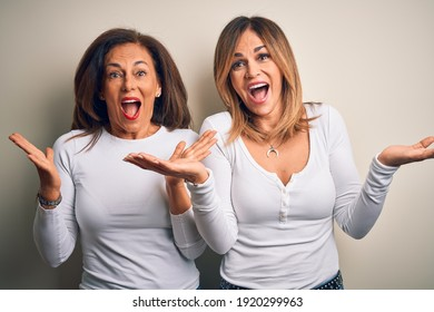 Middle age beautiful couple of sisters wearing casual t-shirt over isolated white background celebrating crazy and amazed for success with arms raised and open eyes screaming excited. Winner concept