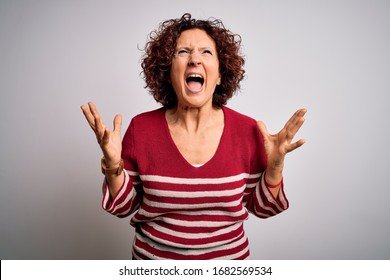 Middle age beautiful curly hair woman wearing casual striped sweater over white background crazy and mad shouting and yelling with aggressive expression and arms raised. Frustration concept.