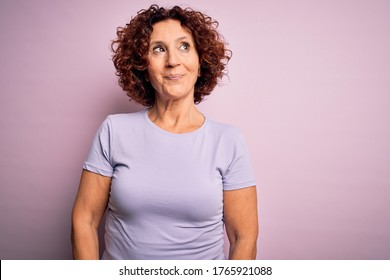 Middle age beautiful curly hair woman wearing casual t-shirt over isolated pink background smiling looking to the side and staring away thinking.