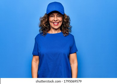 Middle age beautiful delivery woman wearing blue uniform and cap over isolated background with a happy and cool smile on face. Lucky person.