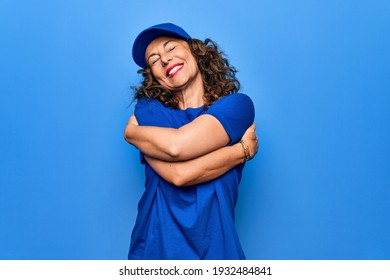 Middle age beautiful delivery woman wearing blue uniform and cap over isolated background hugging oneself happy and positive, smiling confident. Self love and self care
