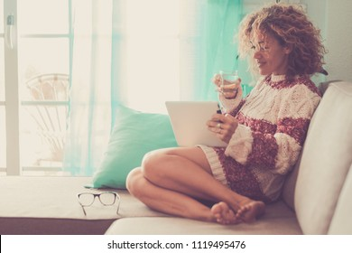 middle age beautiful model woman sitting at home on the sofa reading an ebook on tablet connected with internet. office work indoor alternative lifestyle with independent day and enjoying life