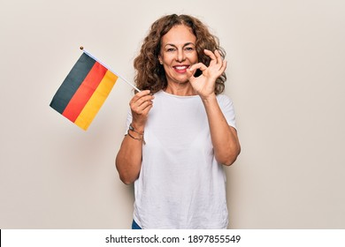 Middle age beautiful patriotic woman holding german flag over isolated white background doing ok sign with fingers, smiling friendly gesturing excellent symbol