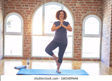 Middle age beautiful sportwoman smiling happy. Standing on mat practicing yoga doing tree pose at gym