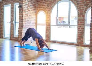 Middle age beautiful sportwoman standing on mat. Practicing yoga doing downward-facing dog pose at gym