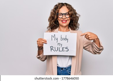 Middle age beautiful woman asking for women rights holding paper with feminist message smiling happy pointing with hand and finger