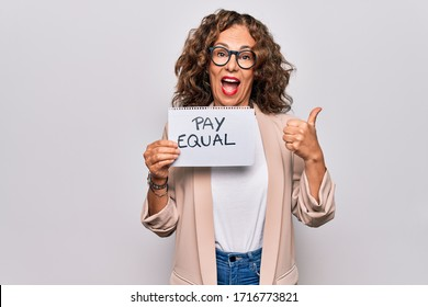 Middle age beautiful woman holding paper with pay equal message over white background pointing thumb up to the side smiling happy with open mouth