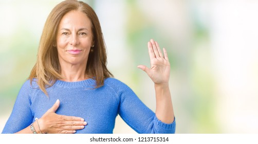 Middle age beautiful woman wearing winter sweater over isolated background Swearing with hand on chest and open palm, making a loyalty promise oath