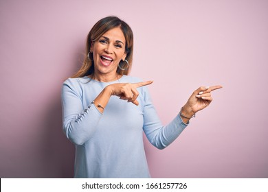 Middle age beautiful woman wearing casual t-shirt standing over isolated pink background smiling and looking at the camera pointing with two hands and fingers to the side.