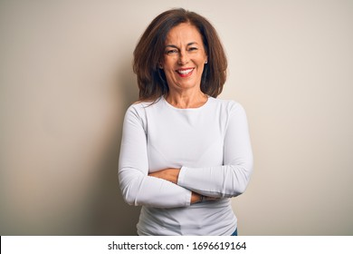 Middle age beautiful woman wearing casual t-shirt standing over isolated white background happy face smiling with crossed arms looking at the camera. Positive person.