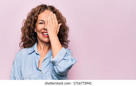Middle age beautiful woman wearing casual denim shirt standing over pink background covering one eye with hand, confident smile on face and surprise emotion.