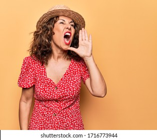 Middle age beautiful woman wearing casual dress and hat over isolated yellow background shouting and screaming loud to side with hand on mouth. Communication concept.