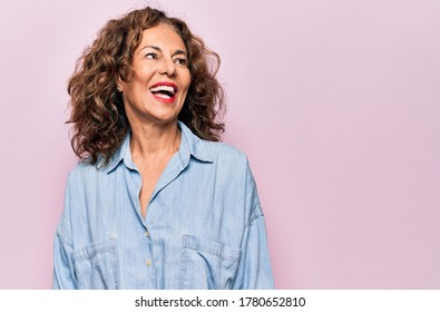Middle age beautiful woman wearing casual denim shirt standing over pink background looking away to side with smile on face, natural expression. Laughing confident. - Shutterstock ID 1780652810