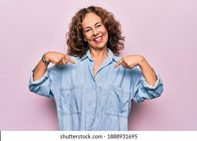 Middle age beautiful woman wearing casual denim shirt standing over pink background looking confident with smile on face, pointing oneself with fingers proud and happy.