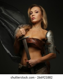 Middle age blond woman holding sword. Isolated on grey