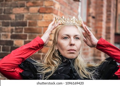 middle age blond woman -queen holding golden crown under head against red brick wall of castle