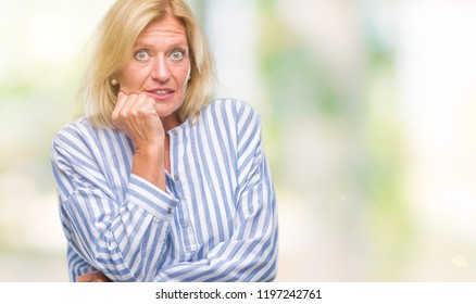 Middle age blonde business woman over isolated background looking stressed and nervous with hands on mouth biting nails. Anxiety problem.