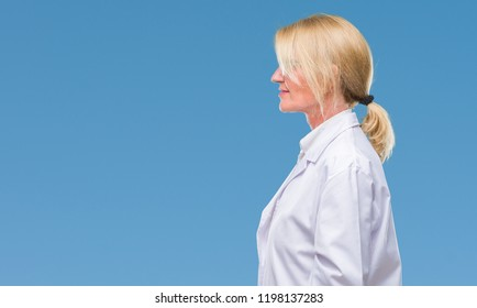 Middle age blonde therapist woman wearing white coat over isolated background looking to side, relax profile pose with natural face with confident smile.