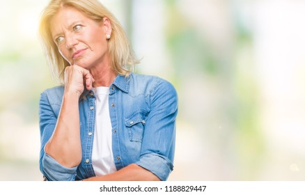 Middle age blonde woman over isolated background thinking looking tired and bored with depression problems with crossed arms.