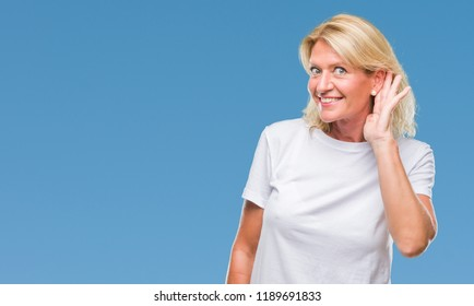Middle age blonde woman over isolated background smiling with hand over ear listening an hearing to rumor or gossip. Deafness concept.