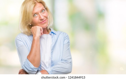 Middle age blonde woman over isolated background with hand on chin thinking about question, pensive expression. Smiling with thoughtful face. Doubt concept.