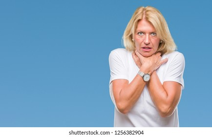 Middle age blonde woman over isolated background shouting and suffocate because painful strangle. Health problem. Asphyxiate and suicide concept.