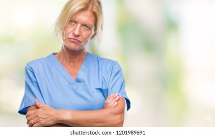 Middle age blonde woman wearing doctor nurse uniform over isolated background skeptic and nervous, disapproving expression on face with crossed arms. Negative person.