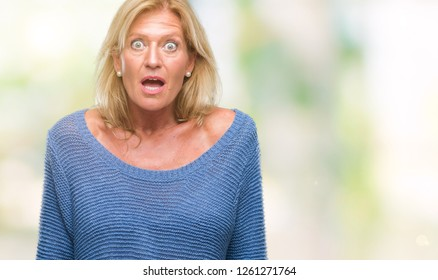 Middle age blonde woman wearing winter sweater over isolated background afraid and shocked with surprise expression, fear and excited face.