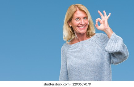 Middle age blonde woman wearing winter sweater over isolated background smiling positive doing ok sign with hand and fingers. Successful expression.