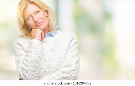 Middle age blonde woman wearing winter sweater over isolated background thinking looking tired and bored with depression problems with crossed arms.
