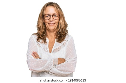 Middle age blonde woman wearing casual white shirt and glasses happy face smiling with crossed arms looking at the camera. positive person.