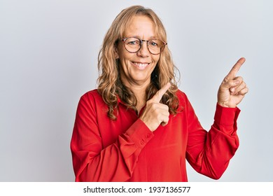 Middle age blonde woman wearing casual clothes and glasses smiling and looking at the camera pointing with two hands and fingers to the side.