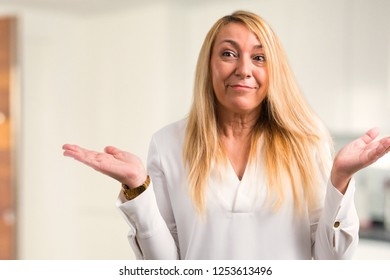 Middle age blonde woman with white shirt having doubts and with confuse face expression while raising hands and shoulders Uncertain concept at home