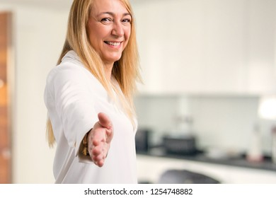 Middle age blonde woman with white shirt handshaking after good deal at home