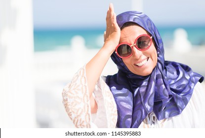 Middle age brunette arabian woman by the pool wearing sunglasses stressed with hand on head, shocked with shame and surprise face, angry and frustrated. Fear and upset for mistake.