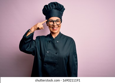Middle age brunette chef woman wearing cooker uniform and hat over isolated pink background Smiling pointing to head with one finger, great idea or thought, good memory