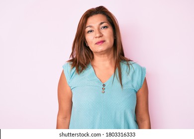Middle age brunette hispanic woman wearing casual clothes relaxed with serious expression on face. simple and natural looking at the camera.
