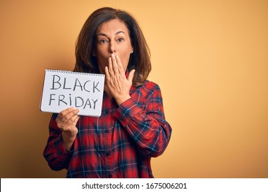 Middle age brunette woman holding black friday paper ad over isolated background cover mouth with hand shocked with shame for mistake, expression of fear, scared in silence, secret concept