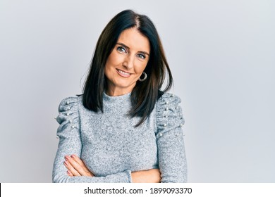 Middle age brunette woman wearing casual clothes happy face smiling with crossed arms looking at the camera. positive person.