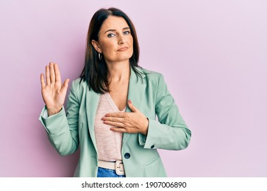 Middle age brunette woman wearing casual clothes swearing with hand on chest and open palm, making a loyalty promise oath