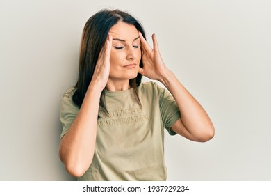 Middle age brunette woman wearing casual clothes with hand on head, headache because stress. suffering migraine.