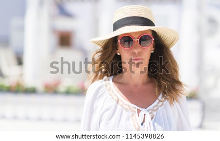 c6b5ff21ac7 Middle age brunette woman wearing sunglasses and summer hat with a  confident expression on smart face